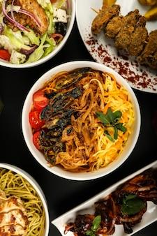Bovenaanzicht noedels met gebakken groenten met tomatensalade en andere gerechten op tafel
