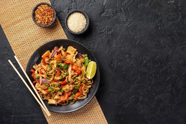 Bovenaanzicht noedels met groenten en kip met kopie ruimte