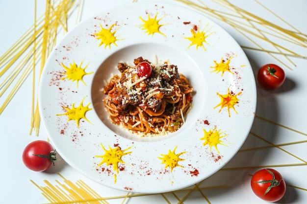 Bovenaanzicht noedels met vlees geraspte kaas en tomaten