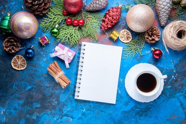 Bovenaanzicht notebook dennenboom takken kegels kerstboom speelgoed op blauwe ondergrond