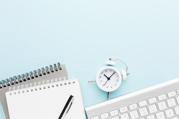Bovenaanzicht notebook en klok arrangement