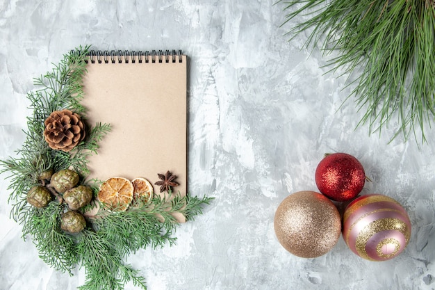 Bovenaanzicht notebook gedroogde schijfjes citroen anijs pijnboom takken kerstboom speelgoed op grijze achtergrond