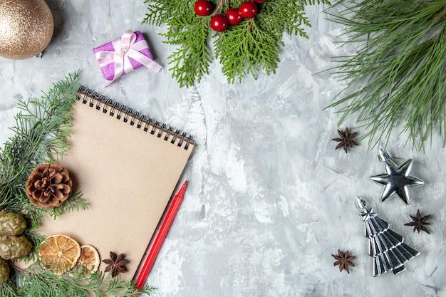 Bovenaanzicht notebook gedroogde schijfjes citroen anijs pijnboom takken rood potlood kerstboom speelgoed op grijze achtergrond vrije ruimte