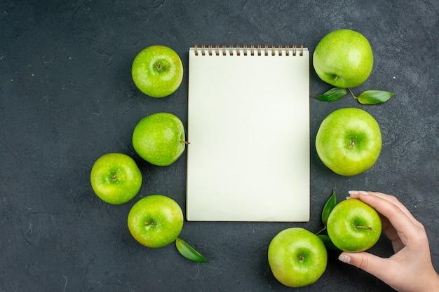 Bovenaanzicht notebook groene appels vrouw hand met appel op donkere ondergrond