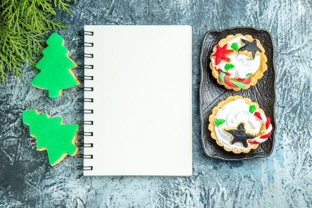 Bovenaanzicht notebook kleine taarten kerstboom koekjes op grijze tafel