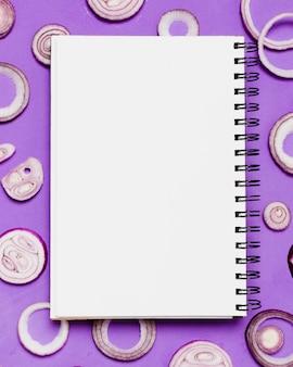Bovenaanzicht notebook met gesneden ui