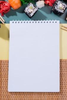 Bovenaanzicht notebook met sushi rolt naast