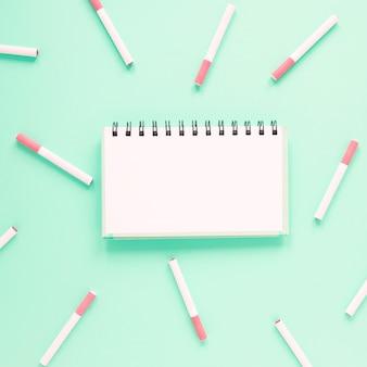 Bovenaanzicht notebook omringd door sigaretten
