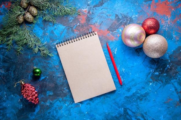 Bovenaanzicht notebook potlood dennenboom takken kegels kerstboom speelgoed op blauwe achtergrond gratis plaats