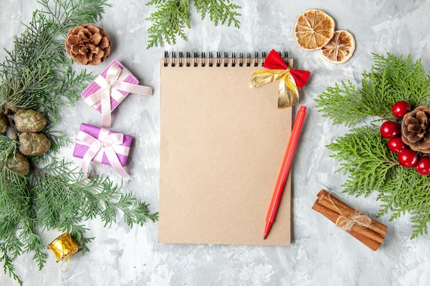 Bovenaanzicht notebook potlood kerstboom speelgoed pijnboom takken op grijze achtergrond