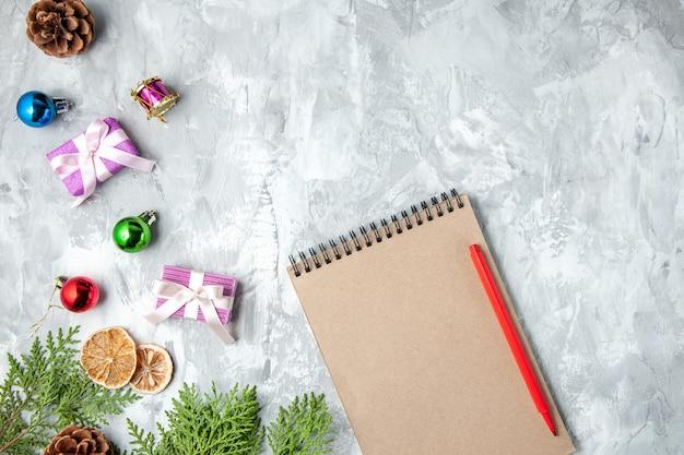 Bovenaanzicht notebook potlood kleine geschenken kerstboom speelgoed op grijze achtergrond vrije ruimte