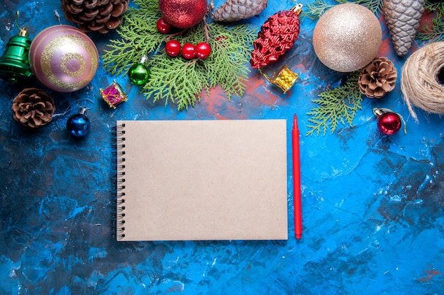 Bovenaanzicht notebook rood potlood dennenboom takken kegels kerstboom speelgoed op blauwe achtergrond gratis plaats