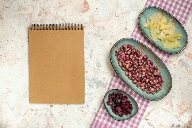 Bovenaanzicht notebook zuurkool bonen gesneden biet op ovale platen op wit en paars geruit tafelkleed op lichtgrijze tafel