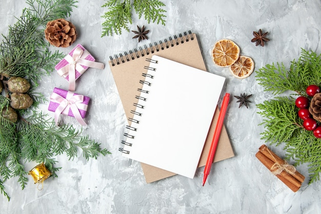 Bovenaanzicht notebooks kerstcadeaus dennenboom takken kaneelstokjes op grijze achtergrond