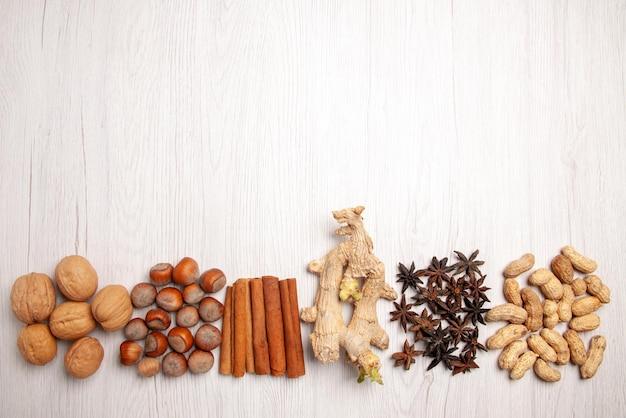 Bovenaanzicht noten en kaneel kaneelstokjes pinda's walnoten hazelnoten op de witte tafel