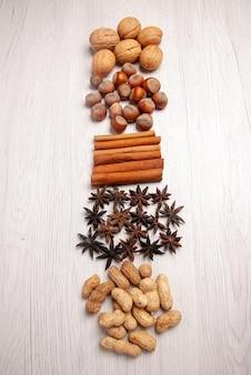 Bovenaanzicht noten en kaneel verschillende soorten noten en kaneelstokjes op de witte tafel