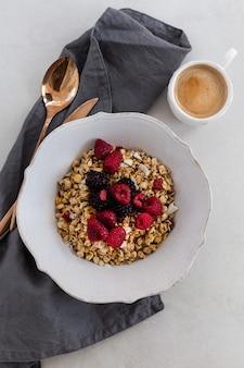 Bovenaanzicht noten in kom met een kopje koffie, framboos, lepel op zwart-wit oppervlak. verticaal