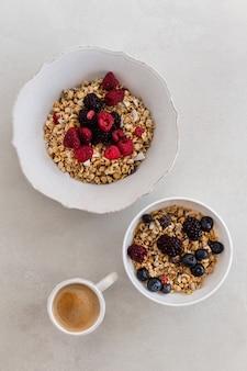Bovenaanzicht noten in kom met een kopje koffie, olijf, framboos op wit oppervlak. verticaal