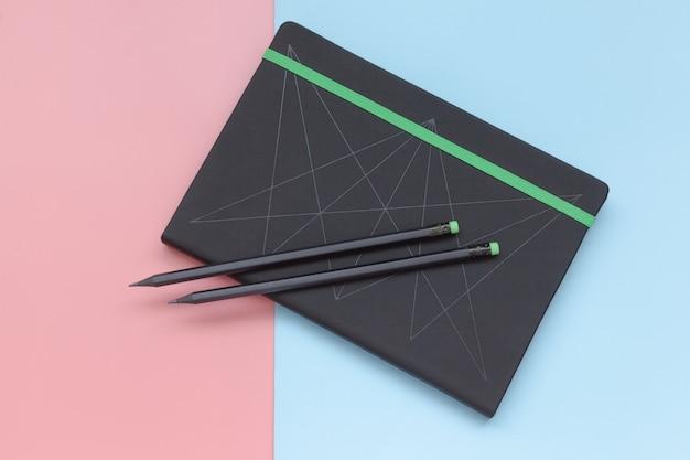 Bovenaanzicht, notitieblok en potlood op roze en blauwe achtergrond.