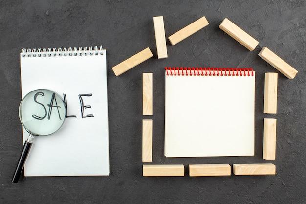 Bovenaanzicht notitieblok in huis vormige houtblokken verkoop geschreven op notebook lupa op zwart