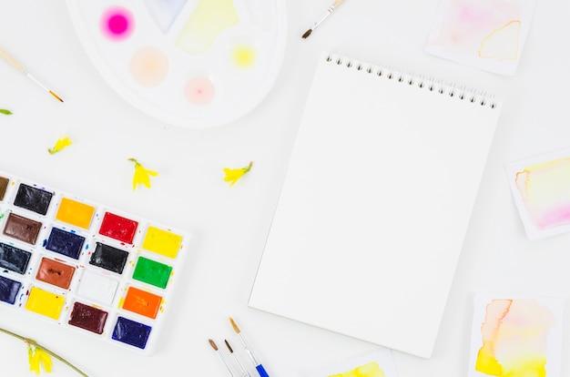 Bovenaanzicht notitieblok met aquarel en bloemblaadjes