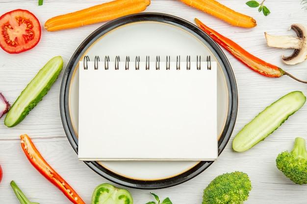 Bovenaanzicht notitieblok op witte plaat gehakte groenten op grijze tafel