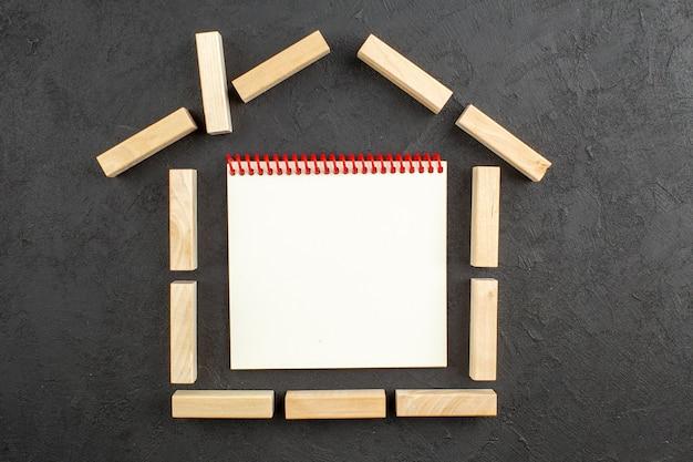 Bovenaanzicht notitieboekje in huisvormige houtblokken op zwart