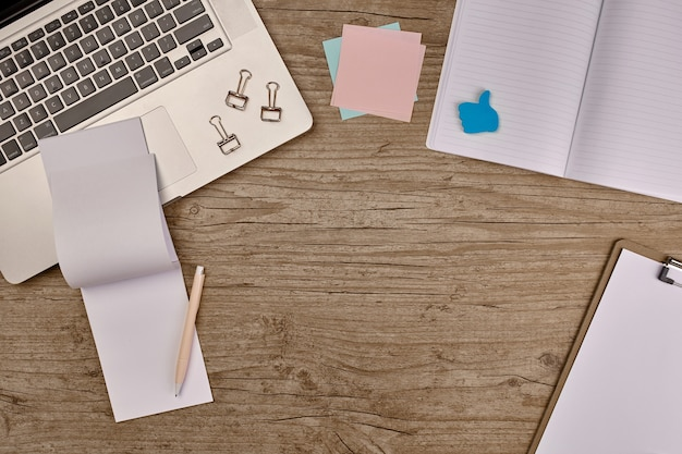 Bovenaanzicht notitieboekje met benodigdheden op houten tafel