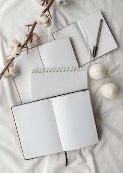 Bovenaanzicht notitieboekjes en katoen arrangement