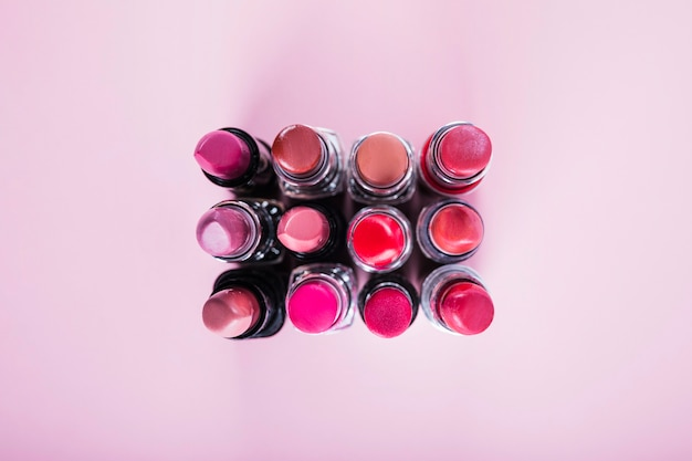 Bovenaanzicht o verschillende kleurrijke lippenstift op roze oppervlak