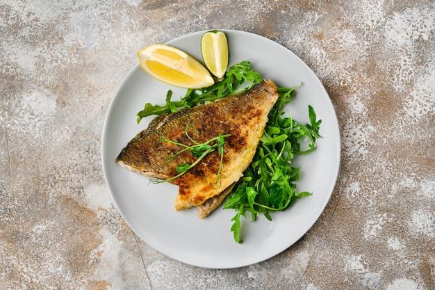 Bovenaanzicht od gebakken dorada vis met verse rucola
