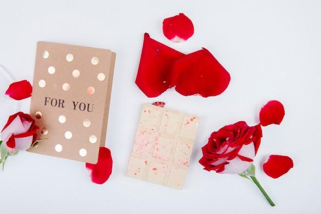Bovenaanzicht od rode roos met kleine ansichtkaart en witte chocolade met rode rozenblaadjes op witte achtergrond