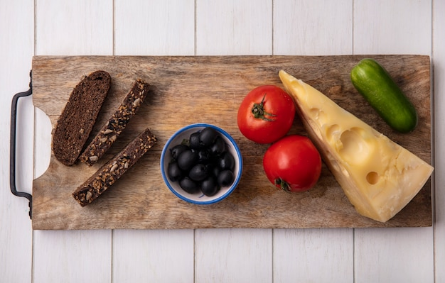 Bovenaanzicht olijven met tomaten, komkommer, zwarte sneetjes brood en kaas op een stand op een witte achtergrond