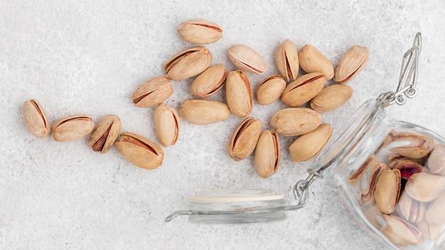 Bovenaanzicht omgekeerde pot gevuld met pistacho op marmeren tafel