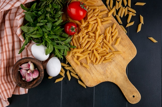 Bovenaanzicht ongekookte pasta met tomaten op een snijplank met eieren knoflook en een bosje munt op een zwarte tafel