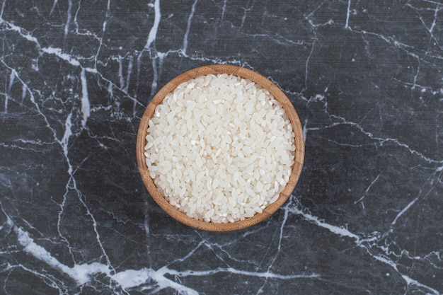 Bovenaanzicht. ongekookte rijst in houten kom.