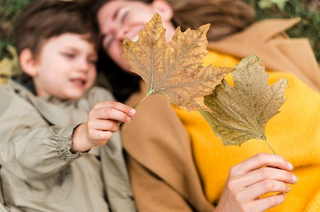 Bovenaanzicht ongericht kleine jongen en moeder spelen met herfstbladeren