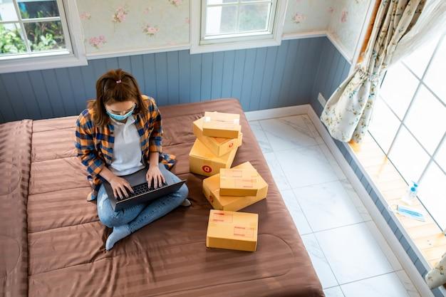 Bovenaanzicht online winkelen jonge vrouwen beginnen een klein bedrijf in een kartonnen doos op het werk.