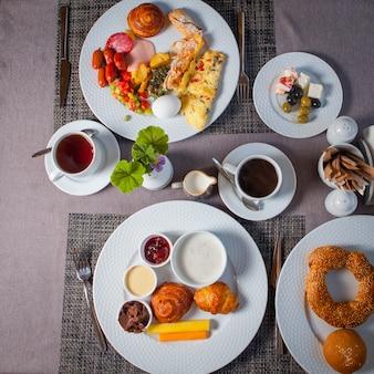 Bovenaanzicht ontbijt eieren, olijven, omelet, croissantjes in borden en kopje thee op tafel