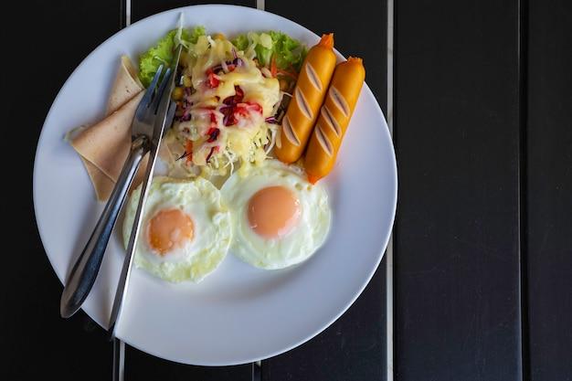 Bovenaanzicht ontbijt met gebakken eieren, spek, worstjes, bonen, toast en frisse salade