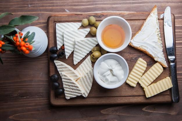 Bovenaanzicht ontbijt met kaas en olijven en honing in board kookgerei