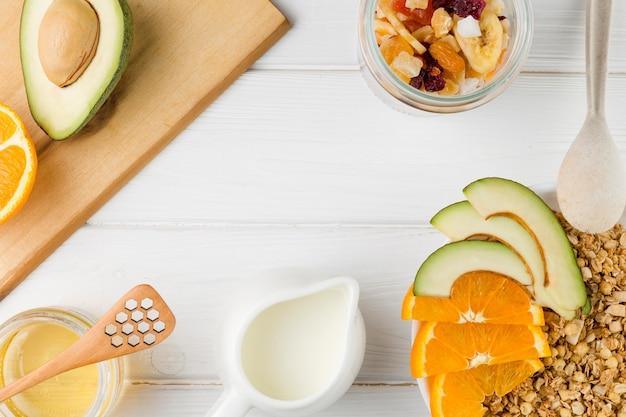Bovenaanzicht ontbijtarrangement met yoghurt en ontbijtgranen