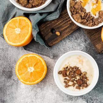Bovenaanzicht ontbijtkom met sinaasappel en granola