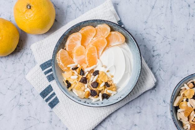 Bovenaanzicht ontbijtkom met yoghurt en sinaasappel