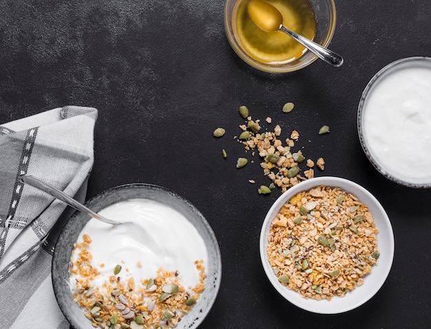 Bovenaanzicht ontbijtkommen met haver en honing