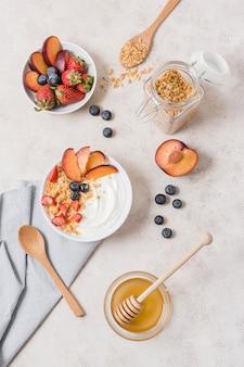 Bovenaanzicht ontbijtkommen met yoghurt en fruit