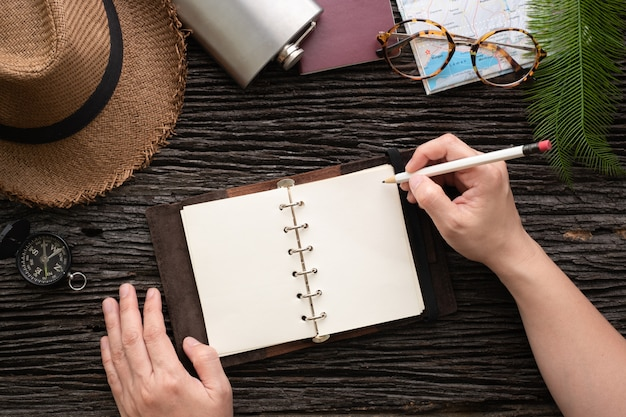 Bovenaanzicht ontdekkingsreiziger hand schrijven op open boek reizen met item