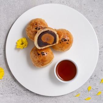Bovenaanzicht ontwerpconcept van maan cake dooier gebak, mooncake voor mid-autumn festival vakantie op donkergrijze tabelachtergrond
