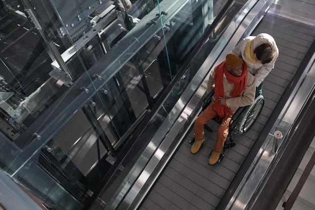 Bovenaanzicht op afro-amerikaanse man in rolstoel die naar beneden gaat in een toegankelijke roltrap in een winkelcentrum of bij een metrostation, kopieer ruimte