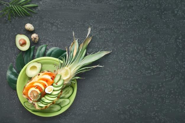 Bovenaanzicht op ananas boot met gerookte zalm en avocado plakjes met citroen en kwartel ei